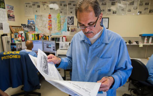 Editor-in-Chief Arnulfo T. Garcia reviewing the San Quentin Newspaper while design editor (background) Phoeun You works on a new edition
